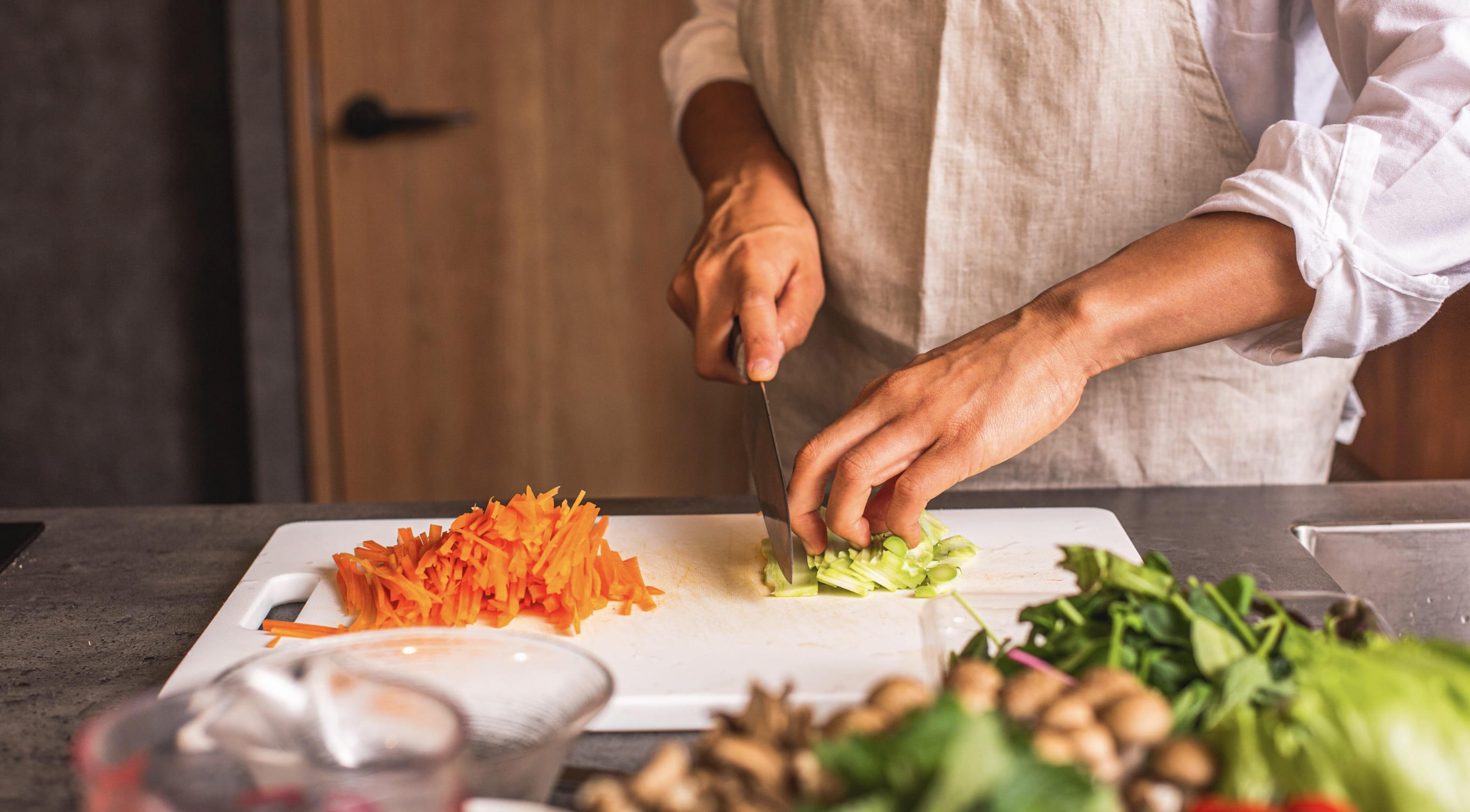 写真:男性が調理をしている手元。まな板の上で野菜を切っている。