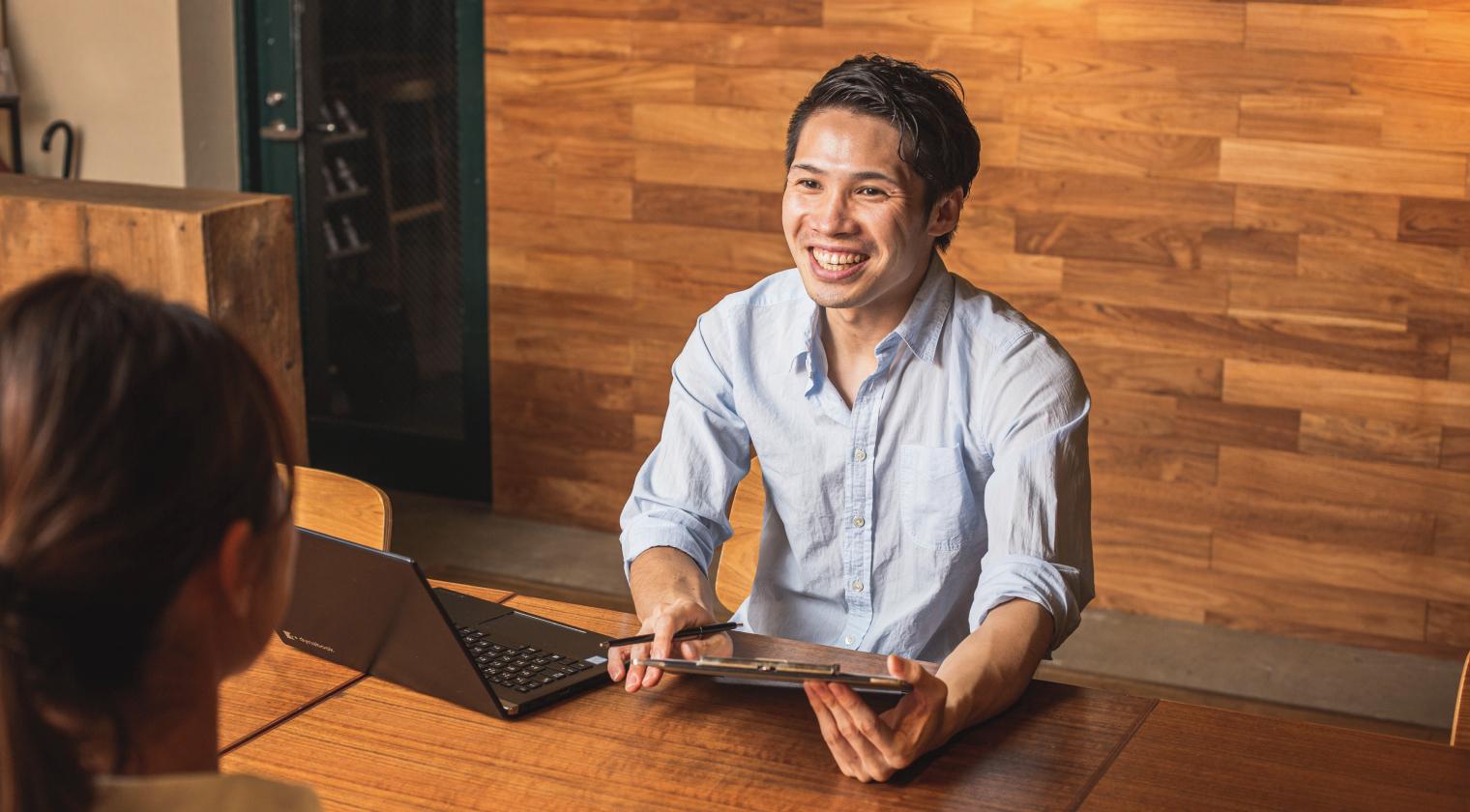 写真:人と会話している男性。手元にはパソコンやバインダー、ペンがある。