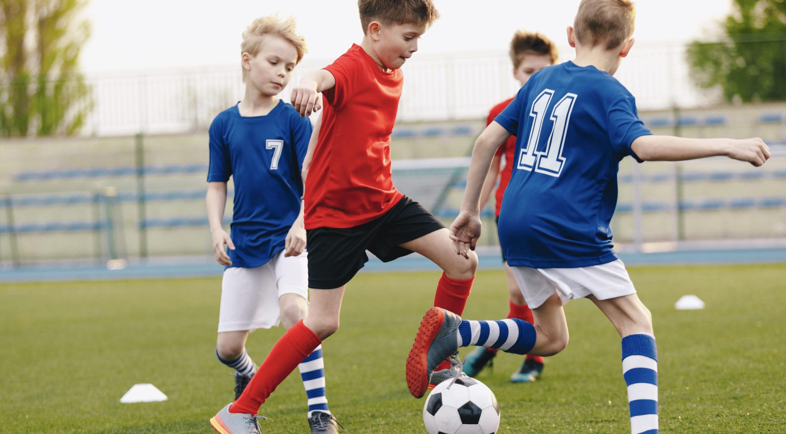 写真:小学生の男の子がサッカーをしている様子、ボールを蹴る瞬間